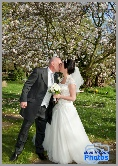 Bride & groom kissing in front of a tree in blossom