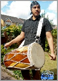 Asian drummer beats the drum outside the groom's house at an Asian wedding