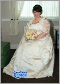 Middle aged bride in her dress awaiting the arrival of the wedding car
