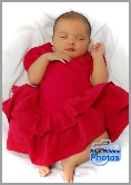 Newborn baby girl in a red dress asleep on a fluffy blanket