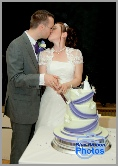 Young wedding couple kissing whilst cutting the wedding cake
