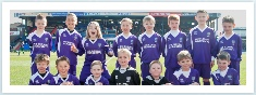 Team photo of Santos Junior football club next to the pitch at Oldham Athletic