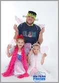 Dad wearing a Frankenstein mask poses with his young daughters