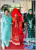 Asian bride arrives at the wedding venue with her face covered in a red veil