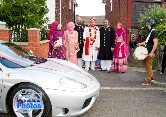 Asian groom makes his way to a silver Ferrari that will take him to his wedding venue
